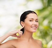 health, spa and beauty concept - clean face of beautiful young woman pointing to her ear