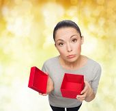 celebration, holidays and happiness concept - disappointed asian woman with empty red gift box