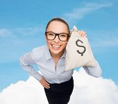 business, money and office concept - smiling businesswoman in eyeglasses holding money bag with doll