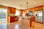 pic of refrigerator  - Bright kitchen with hardwood floor wood cabinets modern steel appliances and tile back splash - JPG