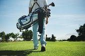 stock photo of golf bag  - Golf man walking with shoulder bag on course in fairway - JPG