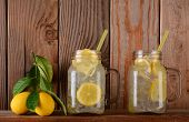 Glasses of lemonade  and lemons on a ledge in front of a rustic wooden kitchen wall. The mason jar s
