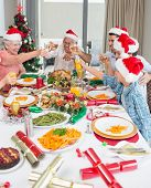 Happy family in santa's hats toasting wine glasses at dining table in the house