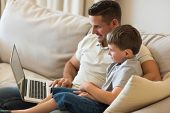 Father and son using laptop while relaxing on sofa at home