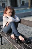 Young Serious Woman On Bench Outdoors