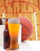 A Basketball Six Pack of Beer Bottles and a Glass of Ale on a white table top with Court in backgrou