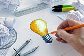 stock photo of compasses  - Designer drawing a light bulb - JPG