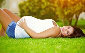 Woman awaiting for a baby, cute pregnant female lying down on fresh green grass in the garden, sunny