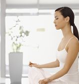 Young woman meditating eyes closed in yoga position indoors.