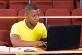 focused male african university student using laptop