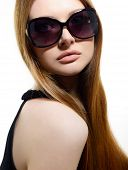 Fashion portrait of young pretty woman wearing sunglasses over white