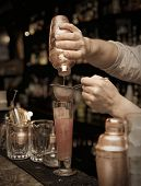 pic of bartender  - Bartender is straining cocktail in highball glass - JPG