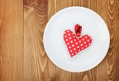 Valentine's Day toy heart over plate. On wooden table background with copy space
