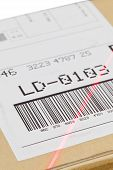 stock photo of barcode  - Barcode on shipping label on box scanned by automatic laser scanner