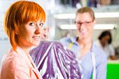 stock photo of laundry  - Customer collecting clothes in laundry shop or textile dry - JPG