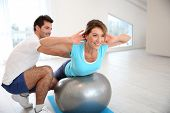stock photo of 35 to 40 year olds  - Woman doing pilates exercises with coach - JPG