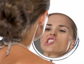 Young Woman Making Funny Faces While Looking In Mirror