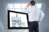 Thinking businessman tilting glasses against room with large window showing city