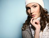 Beautiful young woman posing at studio in white nat and scarf