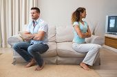 foto of argument  - Full length of young couple having an argument in living room at home - JPG