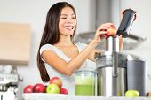Juicing - woman making apple and green vegetable juice using juicer machine at home in kitchen. Heal