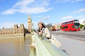 London travel woman tourist by Big Ben and red double decker bus. Girl taking photo on Westminster B