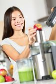 Woman making apple and vegetable juice on juicer machine at home in kitchen. Juicing and healthy eating happy woman making green vegetable and fruit juice. Mixed race Asian Caucasian model.