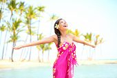 Happy woman praising freedom smiling on hawaiian palm beach in sarong, arms stretched out. Beautiful