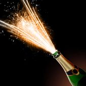 Champagne bottle with blasting fire, isolated on black background