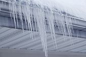 stock photo of gutter  - Icicles hanging on gutter eaves of roof in winter time - JPG