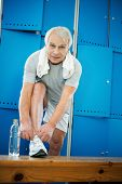 Senior man tying up sneakers in fitness club locker room