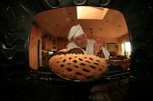 stock photo of pie-in-face  - A Man bakes his signature Smiley Face Cookies in his oven for his hungry family and friends - JPG