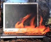 A genuine Lap Top Computer completely engulfed in flames of fire.  Computer damage due to a person t