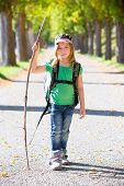 Blond explorer kid girl walking with backpack hiking in autumn trees track holding stick