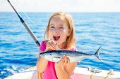 picture of fishing rod  - Blond kid girl fishing tuna little tunny happy with trolling catch on boat deck - JPG