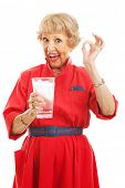 Senior woman holding a glass of ice water and giving the okay sign.  Isolated on white