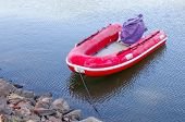 stock photo of outboard  - Red rubber inflatable boat was tightened at the waterside - JPG