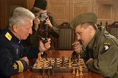 Military mature general playing chess with soldier