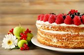 Tasty cake with fresh berries on wooden table