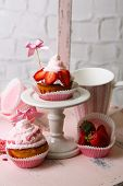 Tasty cup cakes with cream on wooden chair