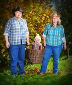 Farmer's family in their orchard. Golden autumn on a countryside.