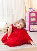 Little Girl In A Beautiful Red Dress Sitting In Her Bedroom