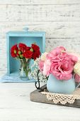 Beautiful flowers in vases on wooden background