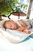 Little Baby Girl Asleep On A Chaise Lounge Outdoors In The Shade
