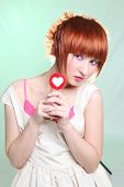 Red-haired girl with lollipop heart on blue background