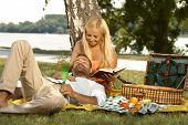 Casual handsome man sleeping at picnic in lap of attractive blonde girlfriend reading a book. Smiling, outdoor, basket.