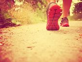 an athletic pair of legs running or jogging on a path during sunrise or sunset toned with a warm in