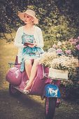 Beautiful blond woman sitting on a retro roller with a book