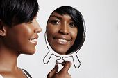 stock photo of mirror  - black woman with a mirror showing at her ideal skin - JPG