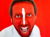 Painted man with red face and white line on nose yelling